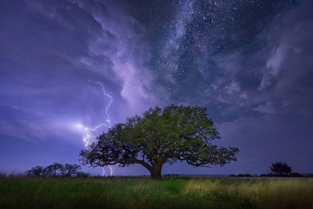 A cloud-to-ground lightning bolt strikes over Albany, Texas as the Milky Way shines above.