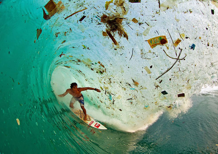 Surfing on a wave full of trash in Java (Indonesia), the world's most populated island