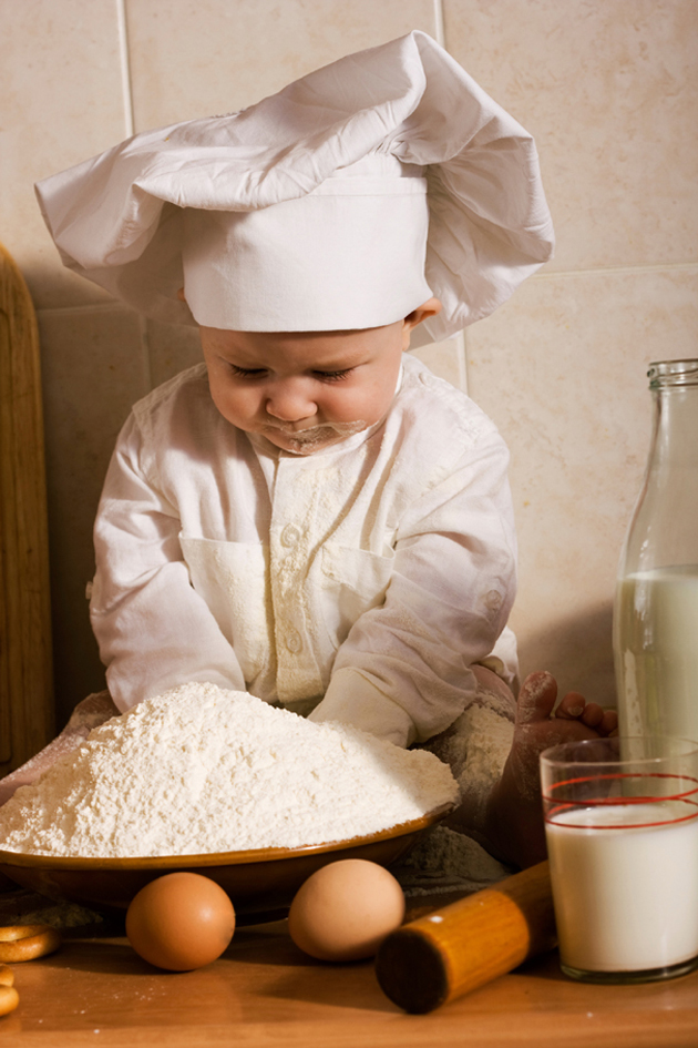 little boy in the cook costume at the kitchen making bread dough. Special toned photo f/x